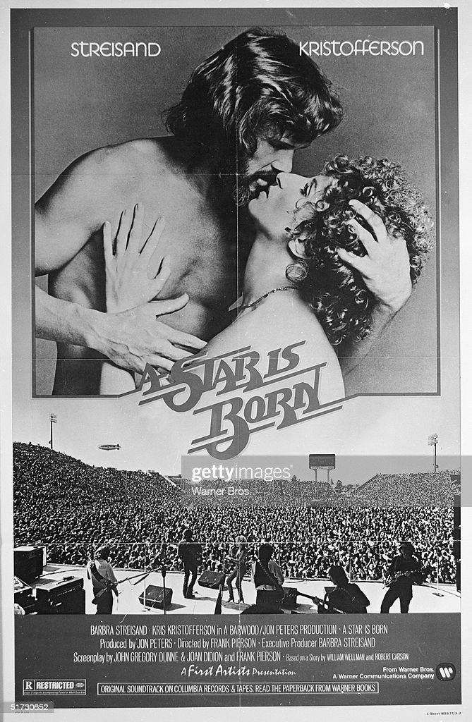 American singers and actors Kris Kristofferson and Barbra Streisand embrace and kiss as they loom over a large crowd at a concert on a movie poster for the film 'A Star is Born' directed by Frank Pierson, 1976.