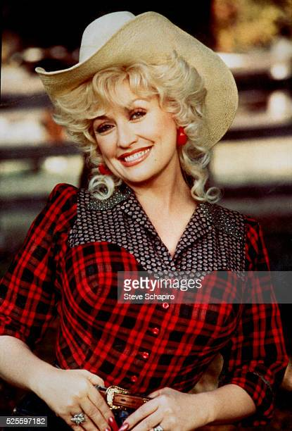 American singersongwriter and actress Dolly Parton wearing a red plaid shirt and a cowboy hat in a publicity portrait for the film 'Rhinestone'...
