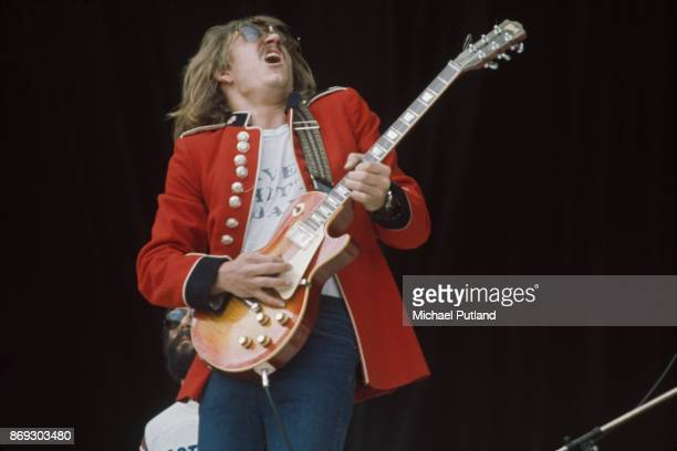 American singersongwriter and guitarist Joe Walsh of rock group Eagles performs on stage wearing a vintage military jacket at Wembley Stadium London...