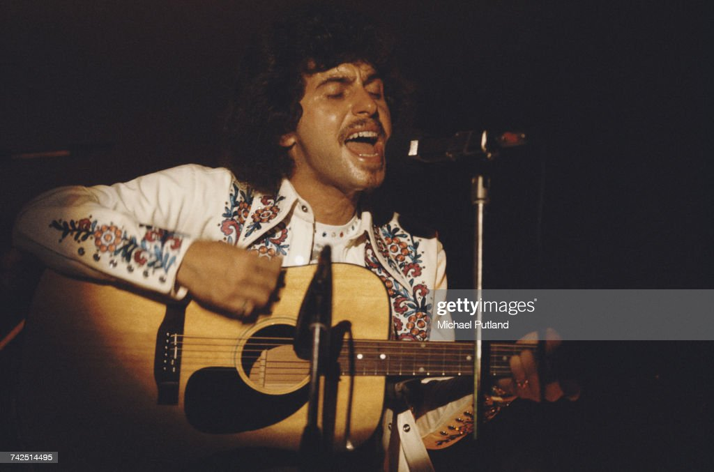 American singer-songwriter and guitarist Johnny Rivers performs live playing an acoustic guitar on stage in London on 11th September 1974.