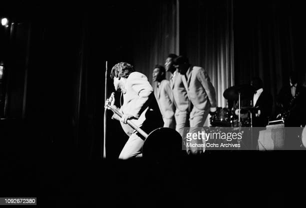 American singersongwriter and musician James Brown performs with the Famous Flames at the Apollo Theatre in New York City 1964