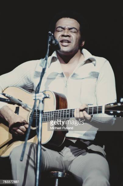 American singer-songwriter Bill Withers performs live on stage playing an acoustic guitar in concert at Hammersmith Odeon in London, 18th November...