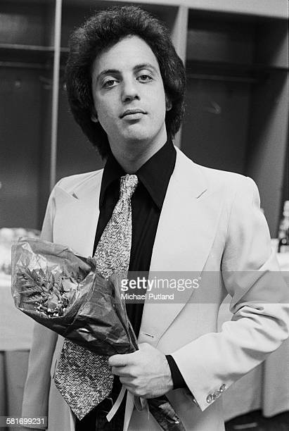 American singer-songwriter Billy Joel holding a bouquet at backstage at a concert in New York City, 7th December 1977.