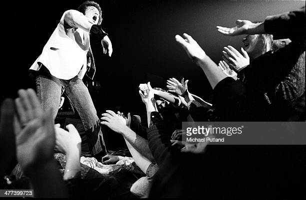 American singer-songwriter Billy Joel performs on stage as the front rows of the audience reach out to him, in New York, 7th December 1977.