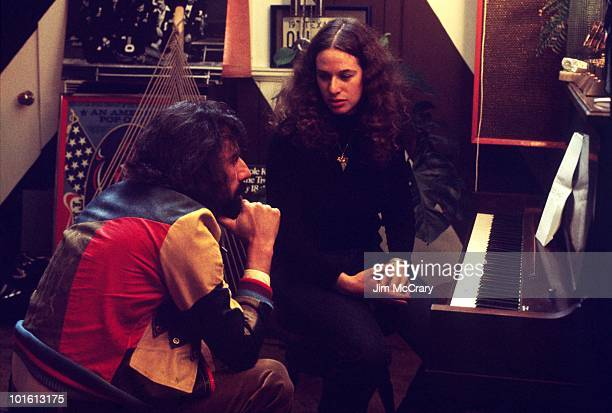 American singersongwriter Carole King sits at a piano talking to recoord producer Lou Adler in his office in March 1971 in Los Angeles California...