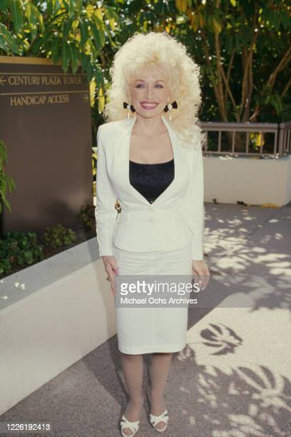 American singer-songwriter Dolly Parton wearing a white two-piece suit and a black top with a scoop neckline, at Century Plaza Towers in Los Angeles,...