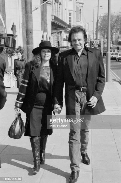 American singer-songwriter, guitarist, actor, and author Johnny Cash walking hand in hand with his wife, American singer, songwriter, actress,...
