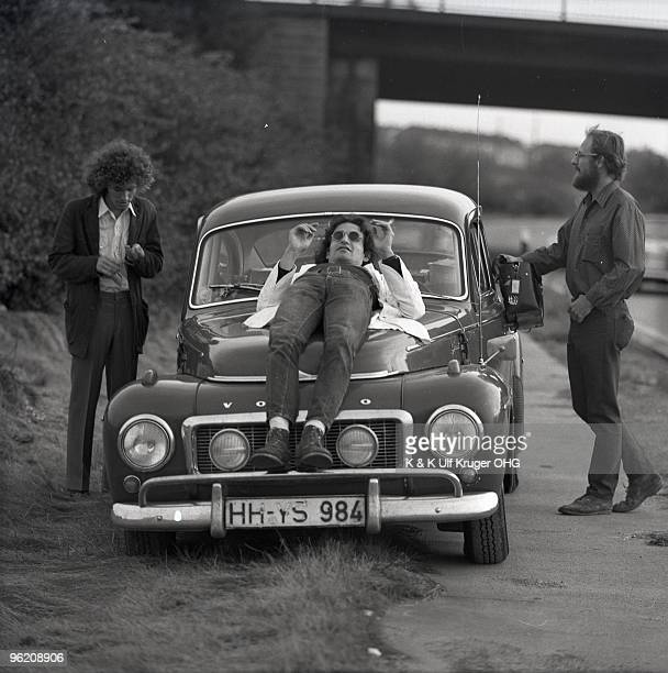 American singersongwriter Tim Buckley David Peel and Lee Underwood stand around a parked Volvo car by a road in September 1968 in Germany