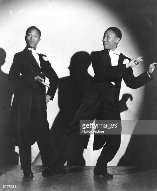 American singing and tap dancing duo The Nicholas Brothers featuring Harold and Fayard Nicholas perform in a spotlight in a promotional portrait for...
