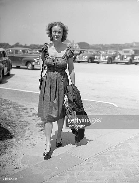 American social activist and diplomat Marietta Tree carries a coat over her arms as she walks to the entrance of the Southampton Bathing Corporation...