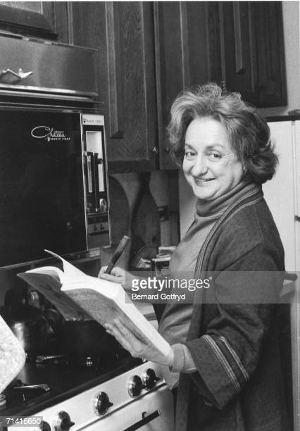 American social activist and writer Betty Friedan turns to look at the camera as she stirs a pot on the stove and holds open a cookbook in a kitchen...