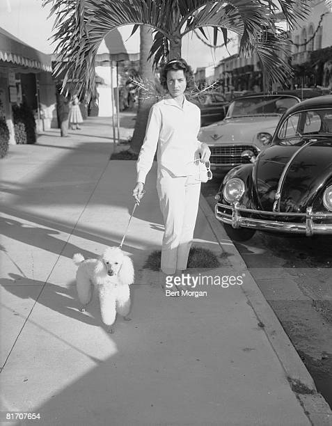American socialite and art collector Jayne Wrightsman walks her pet poodle on Worth Avenue Palm Beach Florida 1960s