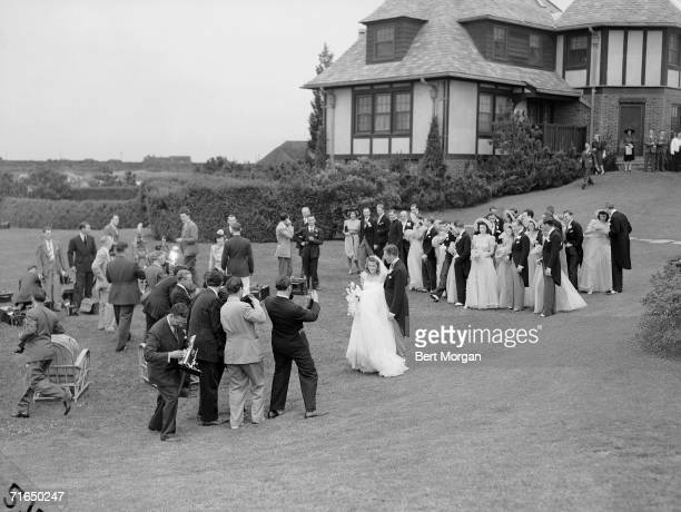 American socialite Anne McDonnell Ford and her new husband automobile executive Henry Ford II pose before a large group of movie and still...