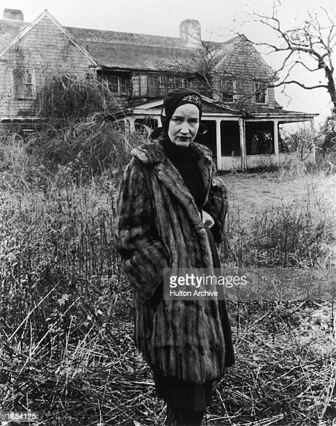 American socialite Edith Beale Jr wears a fur coat while posing in front of her dilapidated East Hampton Long Island mansion in a still from the...