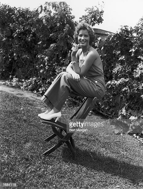 American socialite Edith Beale smokes a cigarette while sitting outdoors in overalls at the East Hampton Fair East Hampton Long Island New York c 1938