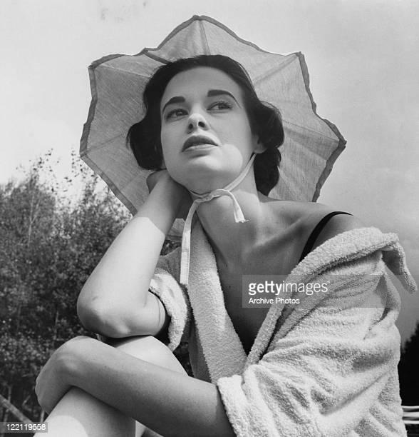 American socialite, fashion designer, actress, writer and artist Gloria Vanderbilt wearing a towelling robe, August 1954.