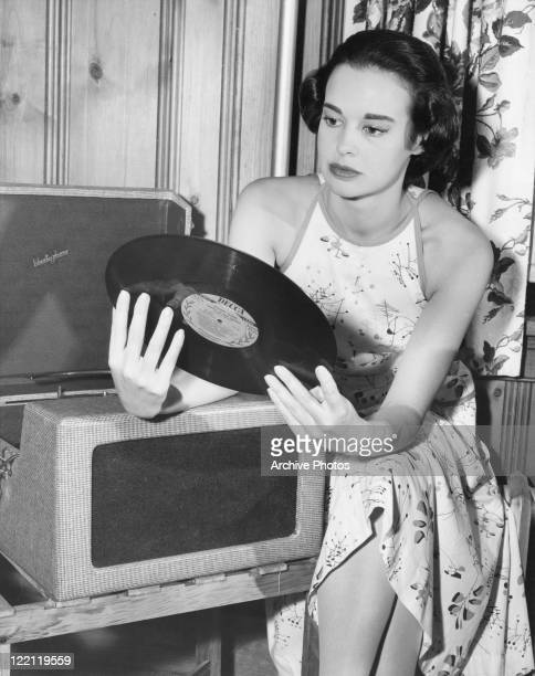 American socialite, fashion designer, actress, writer and artist Gloria Vanderbilt with a Decca long-play record by Richard Tauber entitled 'Songs of...