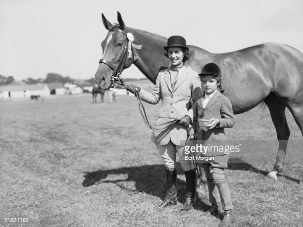 American socialite Janet Lee Bouvier and her young daughter future first lady Jacqueline Bouvier both dressed in riding habits stand on a lawn and...
