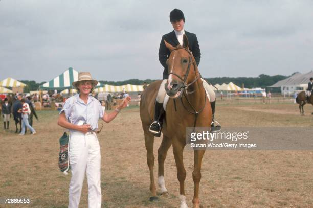 American socialite Jean Kennedy Smith points to her daughter Amanda Mary Smith who sits astride a horse at the Hampton Classic Horse Show...