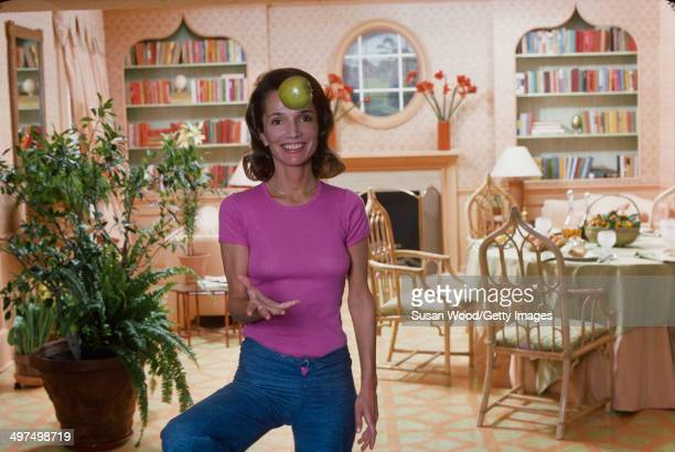American socialite Lee Radziwill smiles as she throws an apple in her dining room, March 1976.