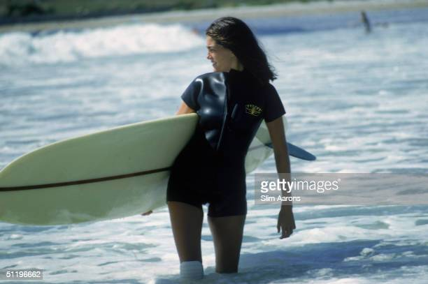 American society girl Minnie Cushing carries her surfboard under her arm September 1965