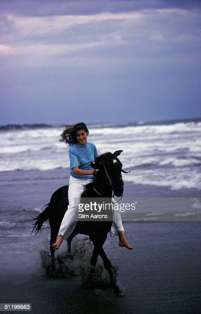 American society girl Minnie Cushing rides her horse along a beach in Acapulco 1972
