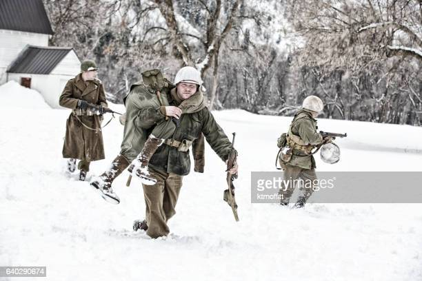 WWII American Soldier Carrying Wounded From A Winter Field