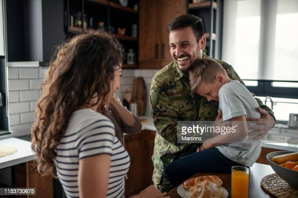 american soldier finally at home with his family - personale militare foto e immagini stock