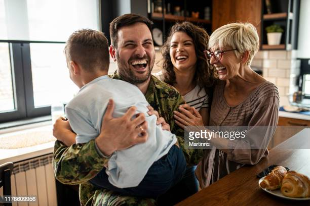 american soldier finally at home with his family - family reunion stock pictures, royalty-free photos & images