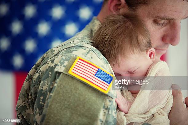 American soldier holding newborn baby