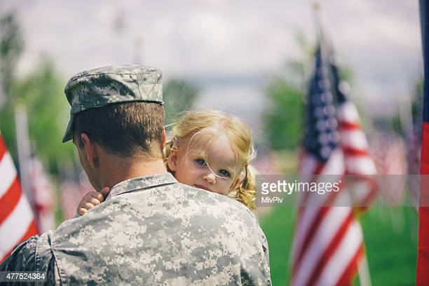 American soldier hugging his toddler daughter