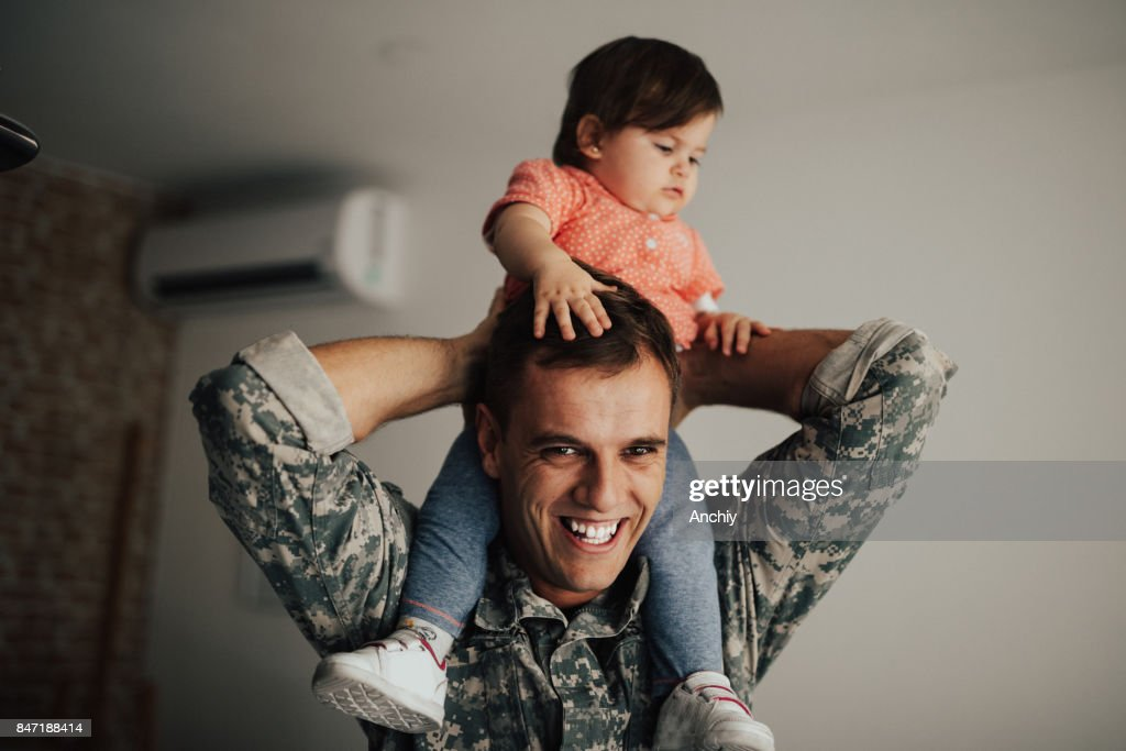 American soldier playing with his daughter : Stock Photo