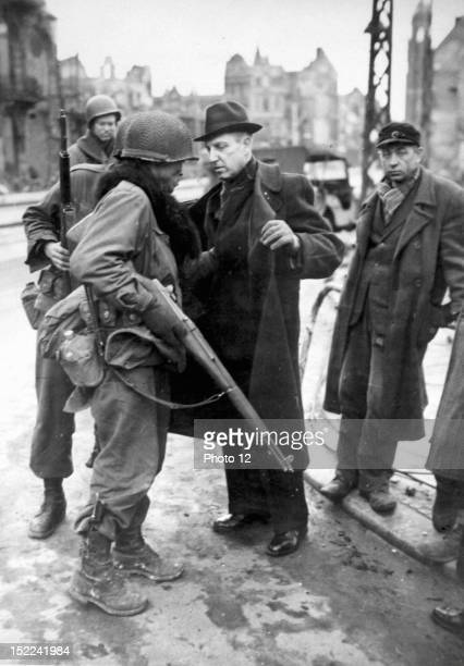A American soldier searches a suspected German civilian who was rounded up on a street corner in Krefeld This city was taken by the 9th US Army...