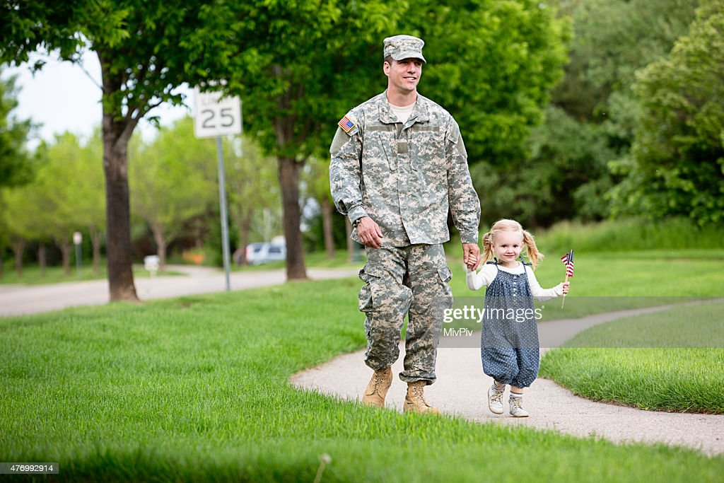 American soldier walking with his daughter : Stock Photo
