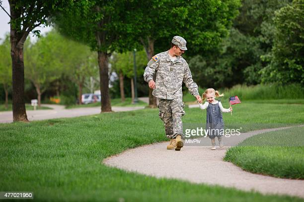 American soldier walking with his daughter