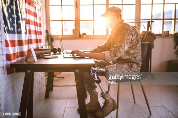 american soldier with prosthetic leg working in his office - veteran stock pictures, royalty-free photos & images