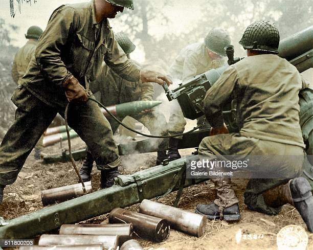 American soldiers are firing a 105mm HM3 Howitzer June 1944 They are from one of three possible infantry regiments of the 4th Infantry Division...