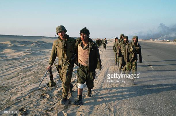 American soldiers are leading captured Iraqi soldiers