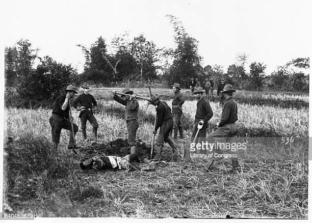 American soldiers bury a corpse during the Philippine Insurrection, an uprising in response to America's colonization of the area following the...