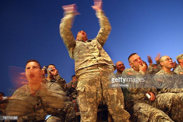 American soldiers cheer as the Dallas Cowboys Cheerleaders take the stage as part of their military USO tour September 15, 2007 in Baghdad, Iraq. The...