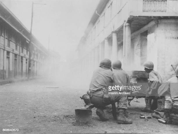 American soldiers fire a 37mm gun towards an enemy position along an unidentified street, near Manila, Philippines, 1945.
