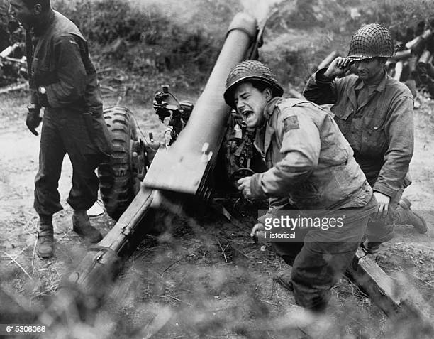 American soldiers fire howitzers at retreating German forces near Carentan France July 11 1944 | Location Caretan France