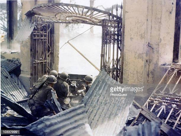 American soldiers from the 189th Infantry Regiment, 37th Division, man an M3 37 mm gun under a damaged metal gate in the Intramuros section of the...