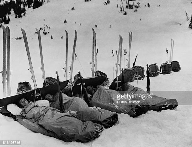 American soldiers from the 503rd parachute ski battalion rest in sleeping bags on the snow after hiking and skiing over rough mountain terrain during...