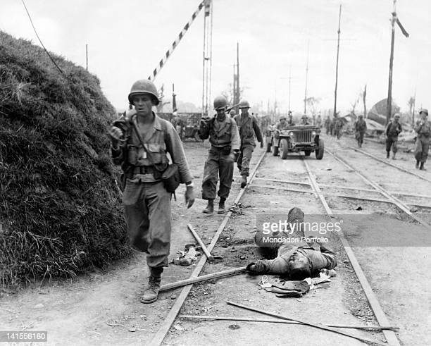 American soldiers from the First Division advancing towards Manila by following the railroad tracks past the body of a dead Japanese Luzon...
