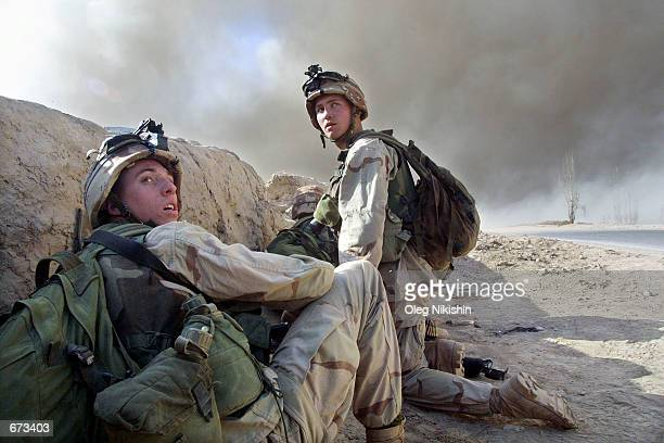 American soldiers hide behind a barricade during an explosion prior to fighting with Taliban forces November 26 2001 at a prison fortress near...