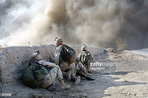 American soldiers hide behind a barricade during an explosion prior to fighting with Taliban forces November 26 2001 at the fortress near...