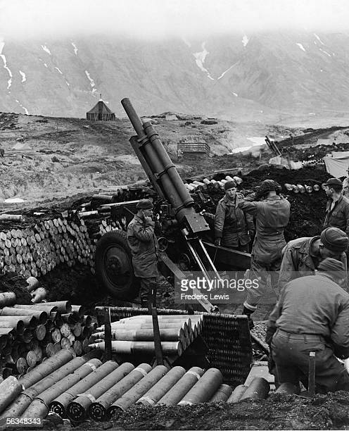 American soldiers in a gun emplacement cover their ears after firing shells from a 105mm howitzer towards Japanese troops positioned in the mountains...