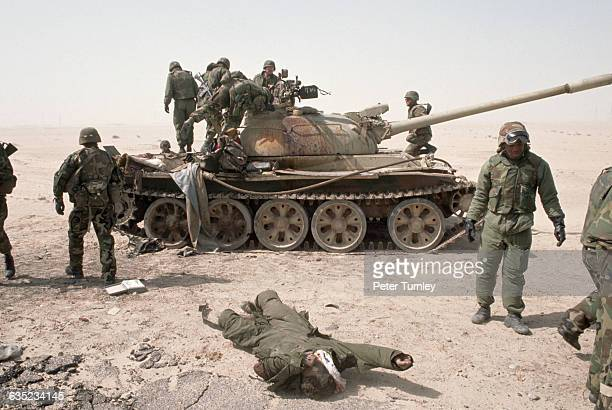 American soldiers in a northern Kuwaiti desert inspect the body of a dead Iraqi soldier and a damaged tank