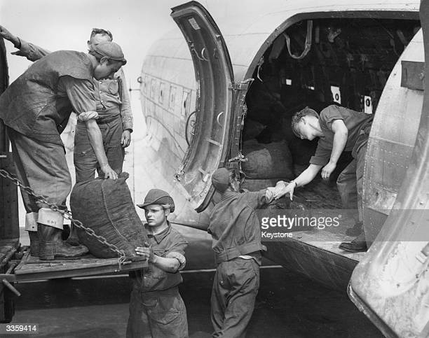 American soldiers load supplies onto a Dakota transport plane bound for the Berlin as part of the Berlin airlift during the Berlin blockade